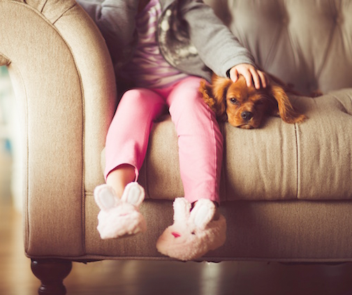 little girl on couch with her dog
