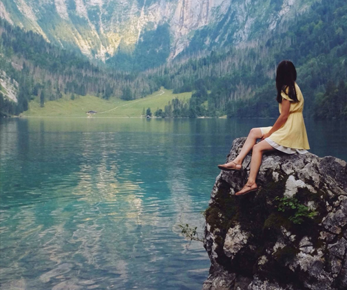 woman sitting on rock overlooking mountains and a lake