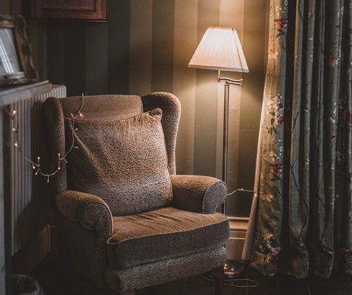 Chair and lamp in corner of dark room