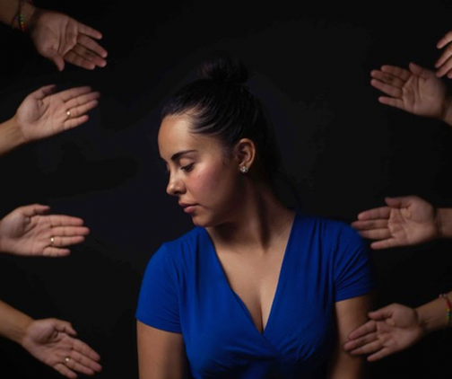 woman surrounded by hands