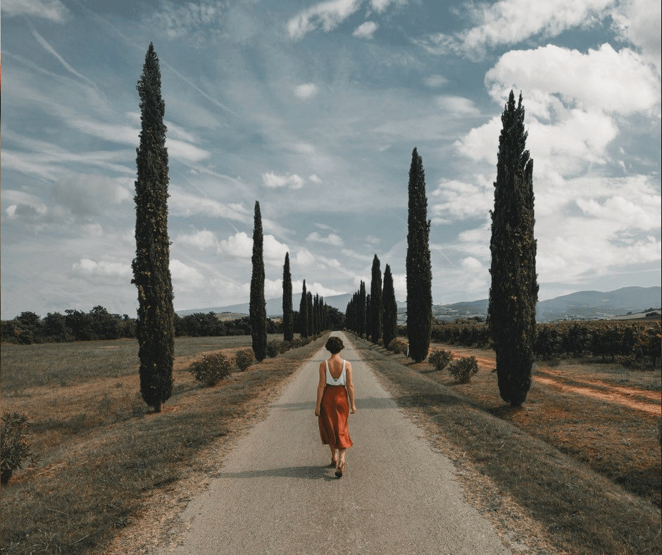 Woman walking down a tree lined path